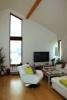 Reference dřevostavby na klíč - obývací prostor s přiznaným stropem a atypickým oknem