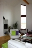 Reference dřevostavby na klíč - obývací pokoj ozvláštňuje atypické okno a zútulňuje krb